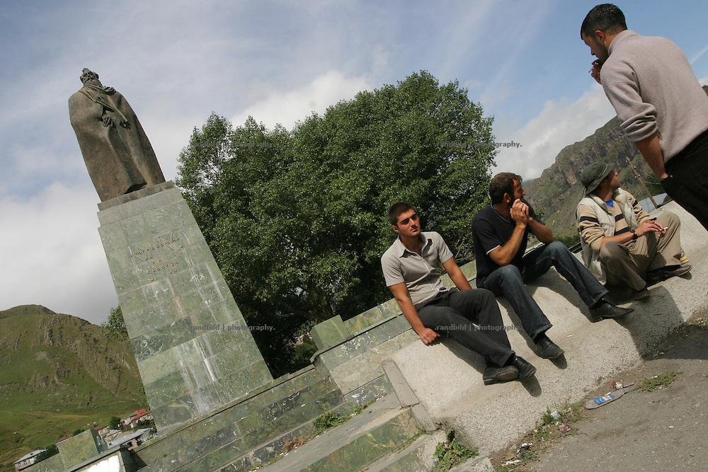 Junge Maenner vor dem Denkmal des georgischen Dichters Kasbegi, nach dem auch das Staedtchen an der Georgischen Heerstrasse benannt ist. ..Young men sitting below an Alexander Kazbegi Statue in Kazbegi, Georgia.
