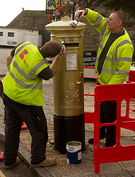 © Licensed to London News Pictures. 02/08/2012. Penzance, UK. Workmen paint a Royal Mail post box in Penzance, the home town of Olympic Gold Medal winner Helen Glover. Helen, along with crew mate Heather Stanning won Great Britain's first Gold medal of the London Olympic games in the women's pairs rowing. Photo credit : Ashley Hugo/LNP