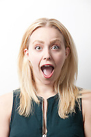 Portrait of shocked young woman screaming against white background