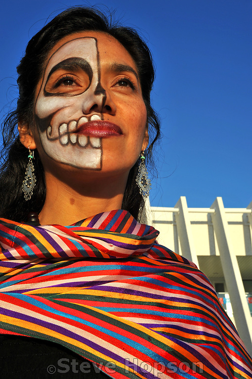 Artist YiuYiu Morales with a painted face at the Día de los Muertos celebration at the Mexican American Cultural Center in Austin Texas, November 1, 2008. Día de los Muertos (Day of the Dead) is a holiday celebrated mainly in Mexico and by people of Mexican heritage focusing on gatherings of family and friends to remember friends and relatives who have died. Traditions include building private altars honoring the deceased, using sugar skulls, marigolds, and the favorite foods and beverages of the departed, and visiting graves with these as gifts.