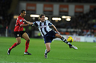 WBA's Jonas Olsson ® beats Cardiff's Peter Odemwingie (l) to clear the ball. Barclays Premier league, Cardiff city v West Bromwich Albion at the Cardiff city Stadium in Cardiff, South Wales on Saturday 14th Dec 2013. pic by Andrew Orchard, Andrew Orchard sports photography.