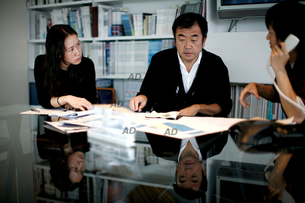 Kengo Kuma, one of the most heralded of a new generation of Japanese architects,  born in Japan in 1954, graduated from the school of engineering at the university of Tokyo in 1979, and continued his studies in New York in 1985-86, at Columbia university. The following year, he founded the ?spatial design? studio and, in 1990, ?kengo kuma & associates?; between 1998 and 1999, he was a professor at the faculty of environmental information at Keio university. Kuma's work is characterized by a delicate simplicity and minimalism, incorporating a wide range of ephemeral transparencies. Their ineffable vibrancy is achieved largely by the extensive and skillful use of screens: metal, wooden, bamboo, and even stone louvers or slates, as well as paper, plastic, and glass surfaces or membranes. His use of new, sophisticated, and efficient technologies, his sensitivity to site, and his attention to the ecological and prevailing social context of his work are all explored in Kengo Kuma. *** Local Caption *** Kengo Kuma in a meeting.