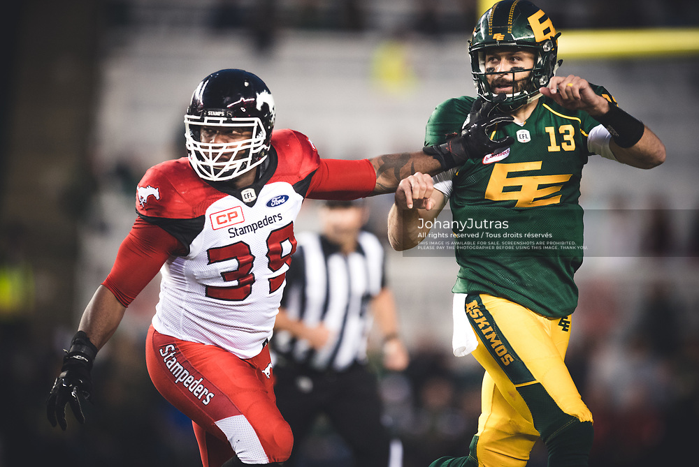 Mike Reilly (13) of the Edmonton Eskimos and Charleston Hughes (39) of the Calgary Stampeders during the game at Commonwealth Stadium in Edmonton AB, Saturday, September 9, 2017. (Photo: Johany Jutras)