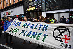© Licensed to London News Pictures. 16/10/2019. London, UK. Dr William Stableforth consultant gastroenterologist and hepatologist and Tracy Lyons a pharmacist hold a banner as Young Extinction Rebellion activists (XR Youth) block the entrance to Google owned Youtube in Kings Cross London, calling for accurate representation on climate change on their platform. Photo credit: Guilhem Baker/LNP
