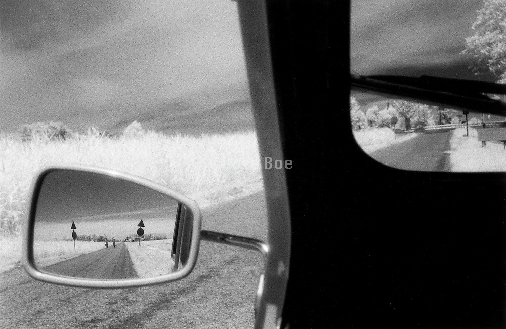 Car rear view mirror reflecting a country road Holland