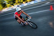 Mario Naranjo Gasteazoro of Panama speeds around the corner at the intersection of Northwest Boulevard and Government Way during the 112-mile bike of Sunday's Ironman Competition in Coeur d'Alene...