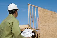 Architect holding blueprints on construction site