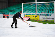 A member of the Eastleigh staff going across the covers with a squeegee before they are removed in the build up to the The FA Cup third round match between Eastleigh and Bolton Wanderers at Silverlake Stadium, Ten Acres, Eastleigh, United Kingdom on 9 January 2016. Photo by Graham Hunt.