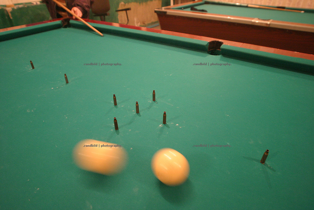 "Ossetische Verteranen spielen Billard mit gewehrkugeln, die Georgier symbolisieren. Südossetien erklärte sich 1990 selbsständig und konnte den folgenden Sezessionskrieg gegen die Georgier für sich entscheiden. Zwischen Georgien und der abtrünnigen Region, die den Anschluß an die Russische Förderation fordert, kommt es trotz des Waffenstillstandsabkommens von 1992 immer wieder zu bewaffneten Ausseinandersetzungen. (Ossetian war verterans playing Bilard with gun bullets. They representing georgians. South Ossetia is a de facto independent republic located within the internationally recognized borders of Georgia. Although this former Soviet autonomous region has declared its independence in 1990. After the following civil war between georgians and ossetians ends in 1992, most parts of the territory is ossetian controlled, while some villages with georgian population are administrated by an georgian ""Alternative Government"".)"