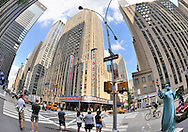 Radio City Music Hall from across the street, and person in Statue of Liberty Costume, Rockefeller Center, midtown Manhattan, NYC, USA, on June 27, 2011. NOTE: 180 degree view taken with fisheye lens. EDITORIAL USE ONLY
