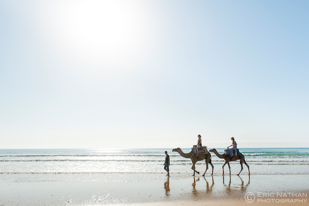 Tourists riding camels along the water's edge of Sidi Kaouki beach in Morocco.