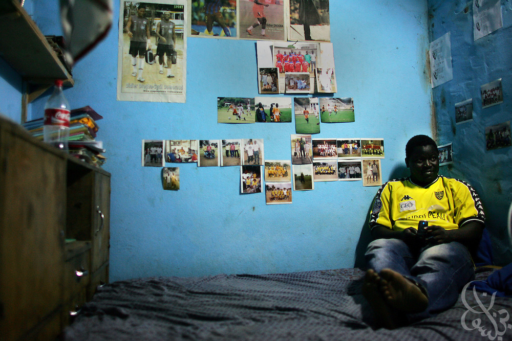 Ivorian Amza Sylla, age 26 sits amid his foootball decorated room in the Abobo neighborhood of Abidjan, Côte d'Ivoire February 18, 2006. Sylla is the founder and director of the Olympic Sport Abobo club one of more than 300 football academies have arisen in Abidjan, amid the success of the ASEC academy.  Sylla also acts as a scout of local football talent for ASEC directors and earns the equivalent of 10 U.S. dollars per player that he recruits for the academy.