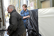 Two men, one in a blue shirt, load a mattress into the back of a moving van at Worth a Second Look in Kitchener, Ontario, Canada. The men are part of Job Cafe, a program of The working Centre, owner of the second hand store.