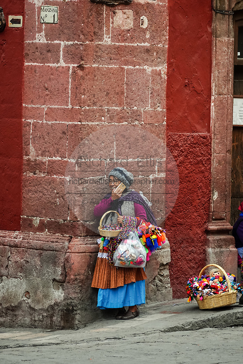 An indigenous woman talks on her mobile phone as she sells handmade crafts in the Plaza Allende in San Miguel de Allende, Guanajuato, Mexico.