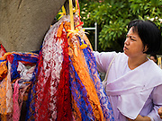 """12 JULY 2014 - PHRA PHUTTHABAT, SARABURI, THAILAND: A woman prays before the Tak Bat Dok Mai at Wat Phra Phutthabat in Saraburi province of Thailand. Wat Phra Phutthabat is famous for the way it marks the beginning of Vassa, the three-month annual retreat observed by Theravada monks and nuns. The temple is highly revered in Thailand because it houses a footstep of the Buddha. On the first day of Vassa (or Buddhist Lent) people come to the temple to """"make merit"""" and present the monks there with dancing lady ginger flowers, which only bloom in the weeks leading up Vassa. They also present monks with candles and wash their feet. During Vassa, monks and nuns remain inside monasteries and temple grounds, devoting their time to intensive meditation and study. Laypeople support the monks by bringing food, candles and other offerings to temples. Laypeople also often observe Vassa by giving up something, such as smoking or eating meat. For this reason, westerners sometimes call Vassa """"Buddhist Lent.""""    PHOTO BY JACK KURTZ"""