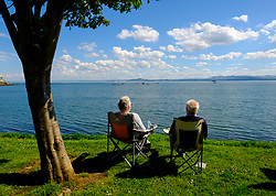 Senior couple enjoy view of Firth of Forth at Aberdour village in Fife, Scotland, UK