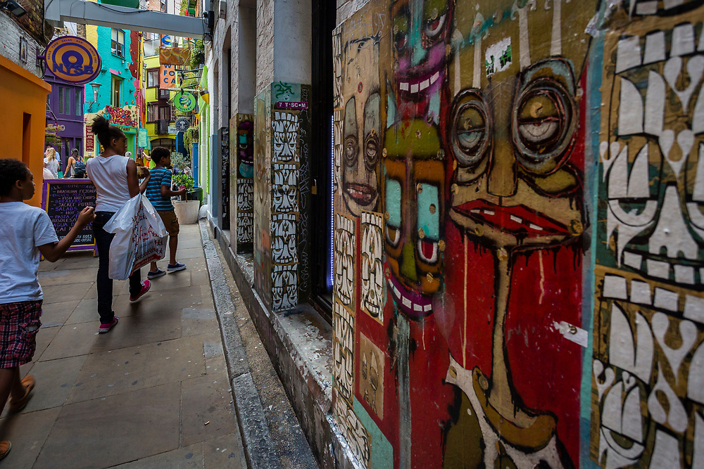 A small alley with grafitti marks the entrance to the colorful Neal's Yard