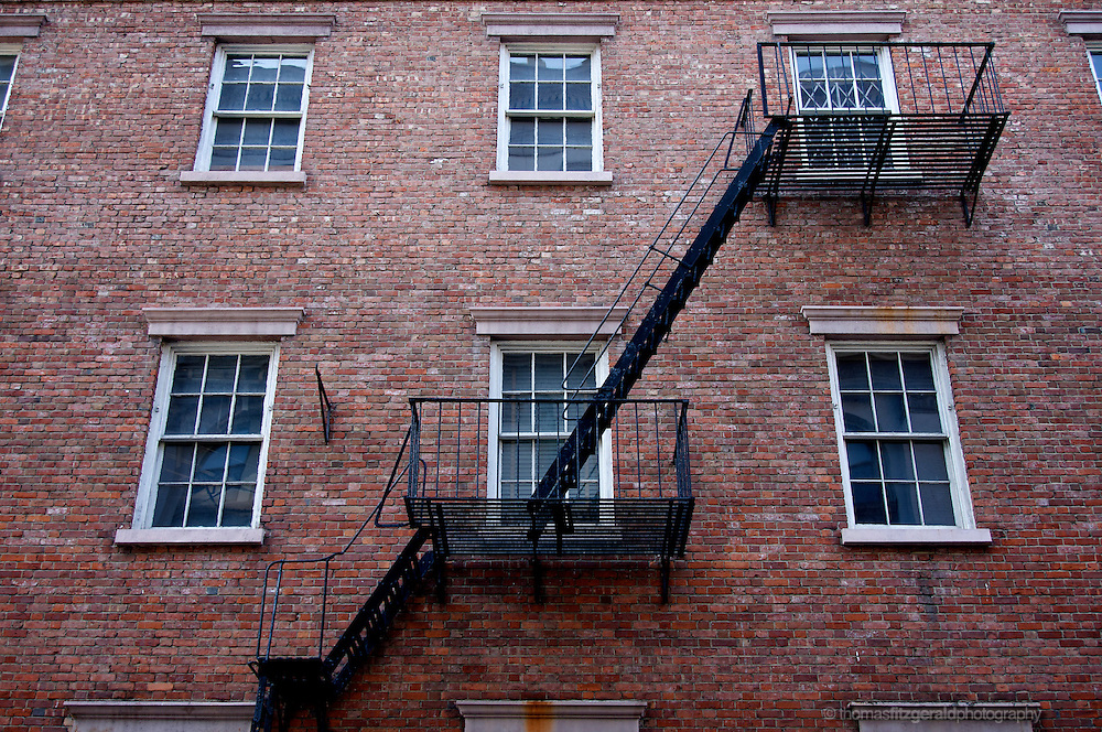 An old fire escape crosses the beautiful brickwork of this down town building in New York