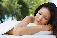 Young woman lying on massage table, outdoors