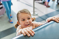 Portrait of young cute little girl being playful in check in at airport