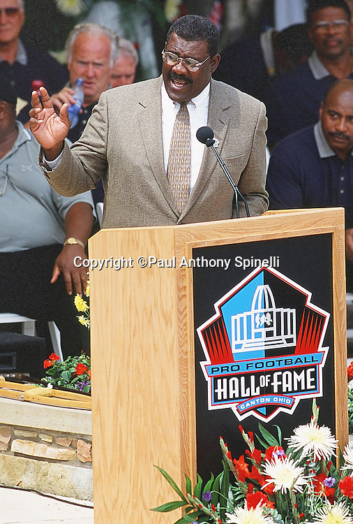 Former Pittsburgh Steelers defensive tackle Joe Greene waves as he speaks at the podium during the NFL Pro Football Hall of Fame Induction Ceremony on July 29, 2000 in Canton, Ohio. (©Paul Anthony Spinelli)