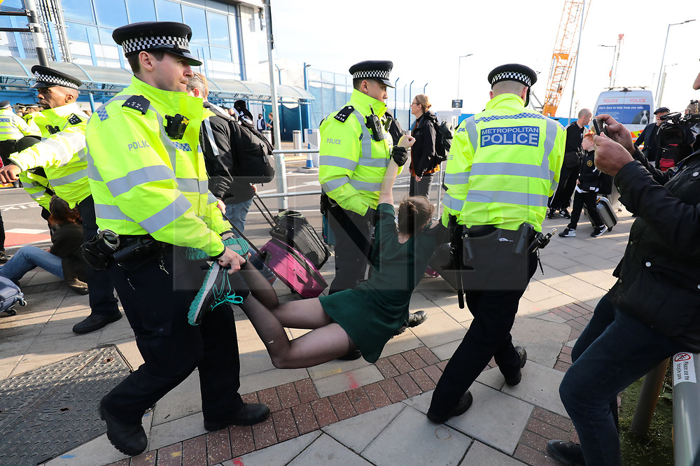 © Licensed to London News Pictures. 10/10/2019. London, UK. Police arrest Extinction Rebellion protesters at London City Airport. Protesters plan to occupy the terminal building in a 'Hong Kong-style' shutdown as part of ongoing protests calling on government departments to tackle the Climate Emergency. Photo credit: Rob Pinney/LNP