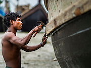 07 NOVEMBER 2014 - SITTWE, RAKHINE, MYANMAR: A Rohingya Muslim worker refurbishes a boat near the port of an IDP camp for Rohingya Muslims near Sittwe. The government of Myanmar has forced more than 140,000 Rohingya Muslims who used to live in Sittwe, Myanmar, into squalid Internal Displaced Person (IDP) camps. The forced relocation took place in 2012 after sectarian violence devastated Rohingya communities in Sittwe and left hundreds dead. None of the camps have electricity and some have been denied access to regular rations for nine months. Conditions for the Rohingya in the camps have fueled an exodus of Rohingya refugees to Malaysia and Thailand. Tens of thousands have put to sea in rickety boats hoping to land in Malaysia but sometimes landing in Thailand. The exodus has fueled the boat building boom on the waterfront near the camps. Authorities expect the pace of refugees fleeing Myanmar to accelerate during the cool season, December through February, when there are fewer storms in the Andaman Sea and Bay of Bengal.   PHOTO BY JACK KURTZ