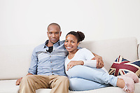 Portrait of happy African American young couple relaxing on sofa