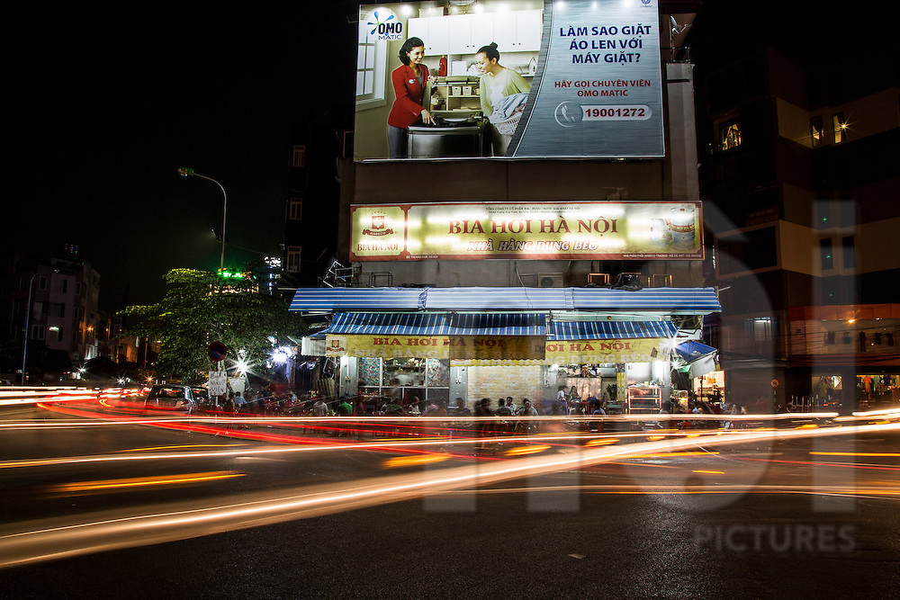 Long exposure of night traffic passing by a bia hoi in Dong Da District, Hanoi, Vietnam, Southeast Asia