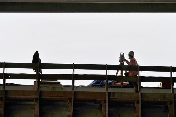 Nederland, Andelst 3-4-2012Wegverbreding van de A50 tussen de knooppunten Ewijk en Valburg. Onderdeel van deze wegverbreding is de bouw van een extra brug over Waal. De laatste brug van deze omvang die Rijkswaterstaat realiseerde, was de Martinus Nijhoffbrug over de Waal bij Zaltbommel in 1995. Mensen bekijken een bord met informatie over de constructie van deze oeververbinding. Een landmeter aan het werk.Foto: Flip Franssen/Hollandse Hoogte