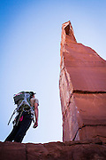 A climber gazes up at The Priest.<br /> Castle Valley, Utah