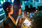 "17 NOVEMBER 2013 - BANGKOK, THAILAND:  A Buddhist novice lights sparklers on a Krathong he was floating in the Chao Phraya River near Wat Yannawa. Loy Krathong (also written as Loi Krathong) is celebrated annually throughout Thailand and certain parts of Laos and Burma (in Shan State). The name could be translated ""Floating Crown"" or ""Floating Decoration"" and comes from the tradition of making buoyant decorations which are then floated on a river. Loi Krathong takes place on the evening of the full moon of the 12th month in the traditional and they do this all evening on the 12th month Thai lunar calendar. In the western calendar this usually falls in November. The candle venerates the Buddha with light, while the krathong's floating symbolizes letting go of all one's hatred, anger, and defilements      PHOTO BY JACK KURTZ"