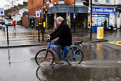 © Licensed to London News Pictures. 15/01/2020. London, UK. A cyclist rides a bike through a flood on Green Lanes in north London following heavy overnight rainfall. Photo credit: Dinendra Haria/LNP