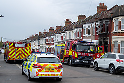 © Licensed to London News Pictures. 16/04/2020. London, UK. Fire engines and a police car parked on Alric Avenue outside a house with a fire damaged facade. The Metropolitan Police Service were called at 02:15BST to a residential address in Alric Avenue NW10 following reports of a fire. Police officers attended with the London Fire Brigade (LFB) and London Ambulance Service (LAS). A 36-year-old woman was taken to hospital with serious injuries. She was pronounced dead at 06:07BST. Another woman, aged in her 60s, was also taken to hospital and treated for non life-threatening injuries. A man in his 40s was arrested on suspicion of arson and taken into police custody. Photo credit: Peter Manning/LNP