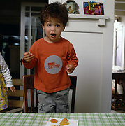 A Latino boy registers surprise while eating a snack of apricots.
