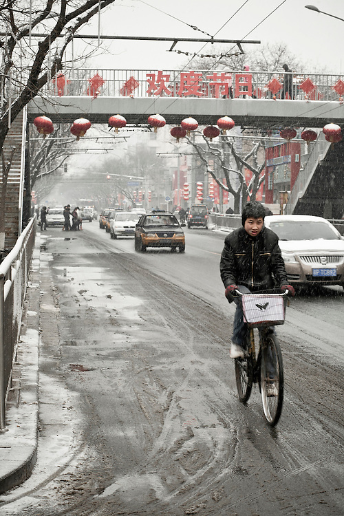 """A young chinese man cycling on the Dongsi avenue in the center of Beijing  after a snowfall that local authorities say they have artifically provoked to fight the exceptional drought in northern China. February 10 2011. On the bridge  the sentence say """"Welcome to the day of the festival"""" , meaning the Spring festival (i.e the chinese new lunar year)just celebrated the february 3."""