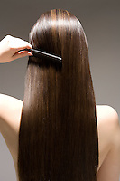 Woman combing long brown hair rear view