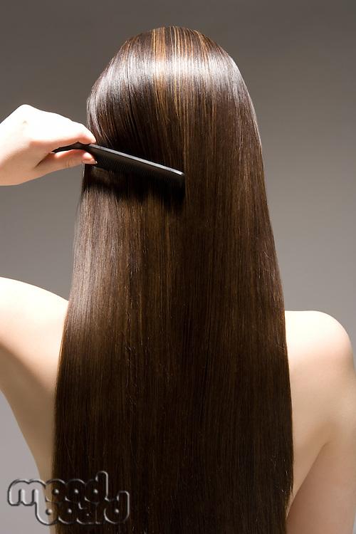 Woman combing long brown hair rear view
