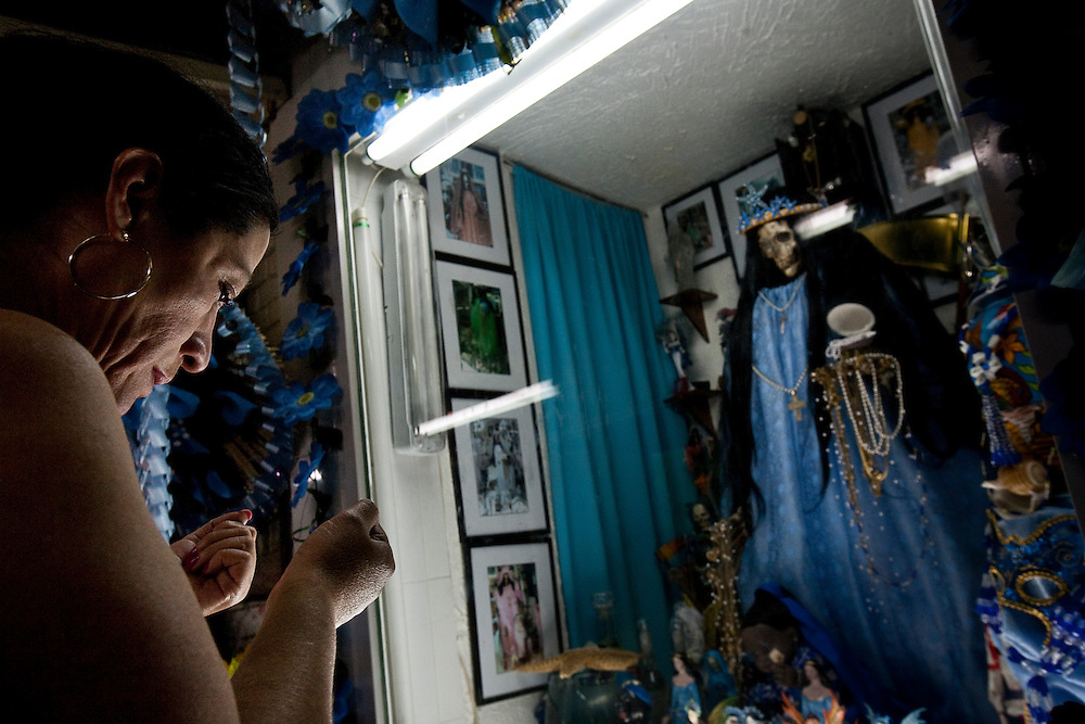 A Sante Muerte devotee prays in front of a popular shrine in Tipito in Mexico City.