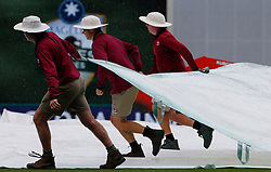 Groundstaff pull on the covers during day one of the Ashes Test match at The Gabba, Brisbane.