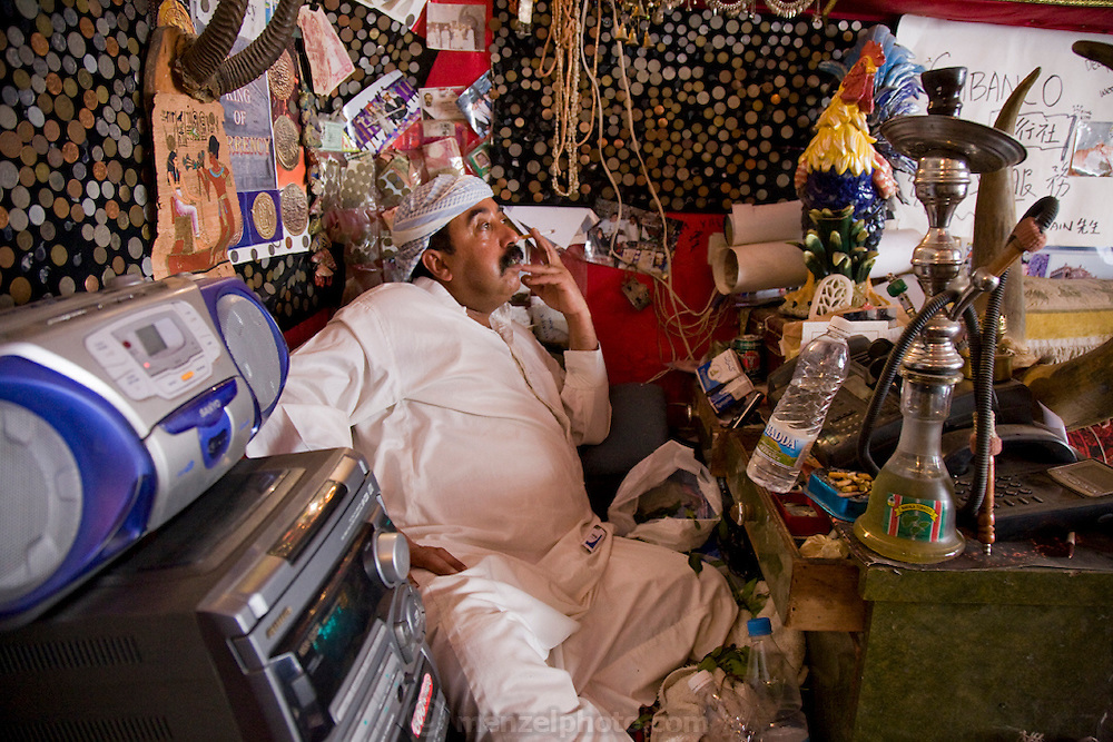 Bashir Sabana's father, in traditional clothing, smokes a cigarette and sits with his hookah in front of him at his market stall in Sanaa, Yemen.  (Bashir Sabana is among the people interviewed for the book What I Eat: Around the World in 80 Diets.)
