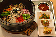 Brooklyn, NY - 26 April 2014. Bibim bop with black sesame tofu at Dotory. The serving bowl is heated on the stovetop, and the dish is served on a wooden trivet.