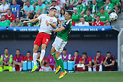Poland Robert Lewandowski beats Northern Ireland Craig Cathcart in the air for a header during the Euro 2016 match between Poland and Northern Ireland at the Stade de Nice, Nice, France on 12 June 2016. Photo by Phil Duncan.