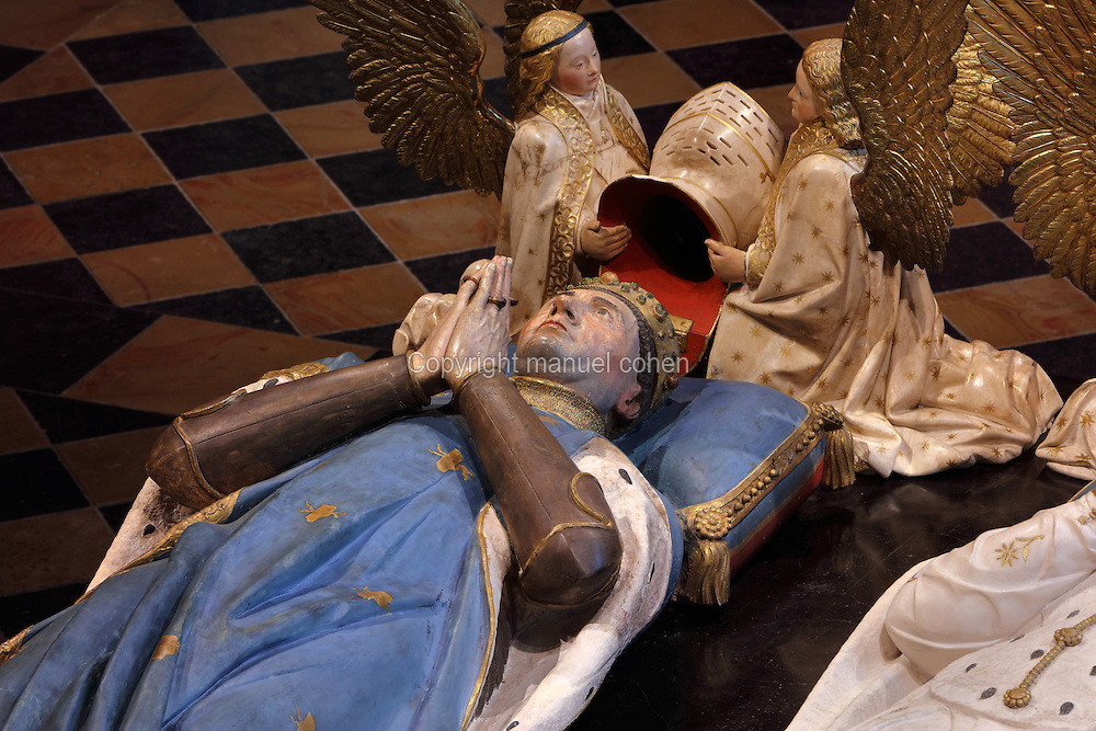 Effigy of John the Fearless with angels holding helmet, from the tomb of Jean sans Peur, or John the Fearless, 1371-1419, (Jean de Valois or John of Valois, Jean I, duc de Bourgogne, or John I, Duke of Burgundy) and his wife Marguerite de Baviere, or Margaret of Bavaria, 1363- 1423, 1443-70, by Jean de la Huerta, 1413-62, and Antoine le Moiturier, 1425-97, in the Grande Salle du Palais des ducs de Bourgogne, or Salle des Gardes, a 15th century Flamboyant Gothic hall, in the Musee des Beaux-Arts de Dijon, opened 1787 in the Palace of the Dukes of Burgundy in Dijon, Burgundy, France. The tomb consists of painted alabaster effigies with lions and angels, and below, figures of pleurants or weepers among Gothic tracery. The tomb was begun in 1443 (24 years after his death), by Jean de La Huerta, and Antoine le Moiturier after 1456, and finally installed in 1470. The tombs were originally from the Chartreuse de Champmol, or Chartreuse de la Sainte-Trinite de Champmol, a Carthusian monastery which was sacked in the French Revolution and the tombs moved to Dijon cathedral then here in 1827. The effigies are 19th century reconstructions, the originals being destroyed in the French Revolution. Picture by Manuel Cohen