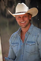 good looking blond and blue eyed cowboy smiling
