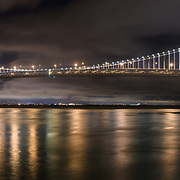 The lights of the San Francisco-Oakland Bay Bridge shimmer on the bay; as seen from pier 14 along the embarcadero.