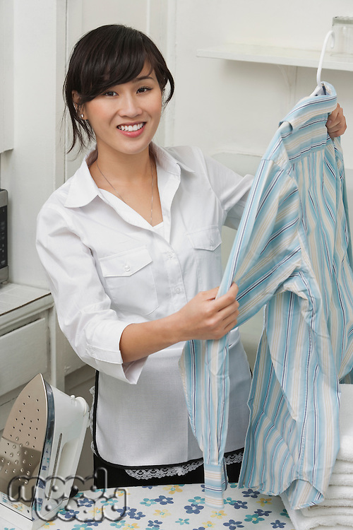 Portrait of young housemaid holding shirt