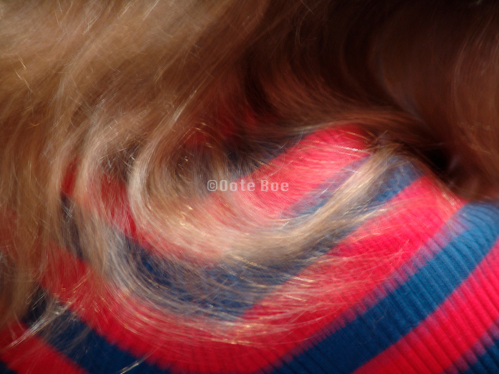 close up of a woman?s hair falling over her shoulder.