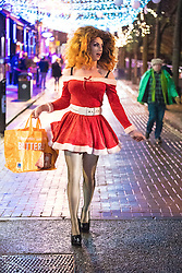"© Licensed to London News Pictures . 23/12/2016 . Manchester , UK . A man , dressed as a woman , dressed as Santa Claus , walks along Canal Street . Revellers out in Manchester City Centre overnight during 2016's second "" Mad Friday "" , named for historically being one of the busiest nights of the year for the emergency services in the UK . Photo credit : Joel Goodman/LNP"
