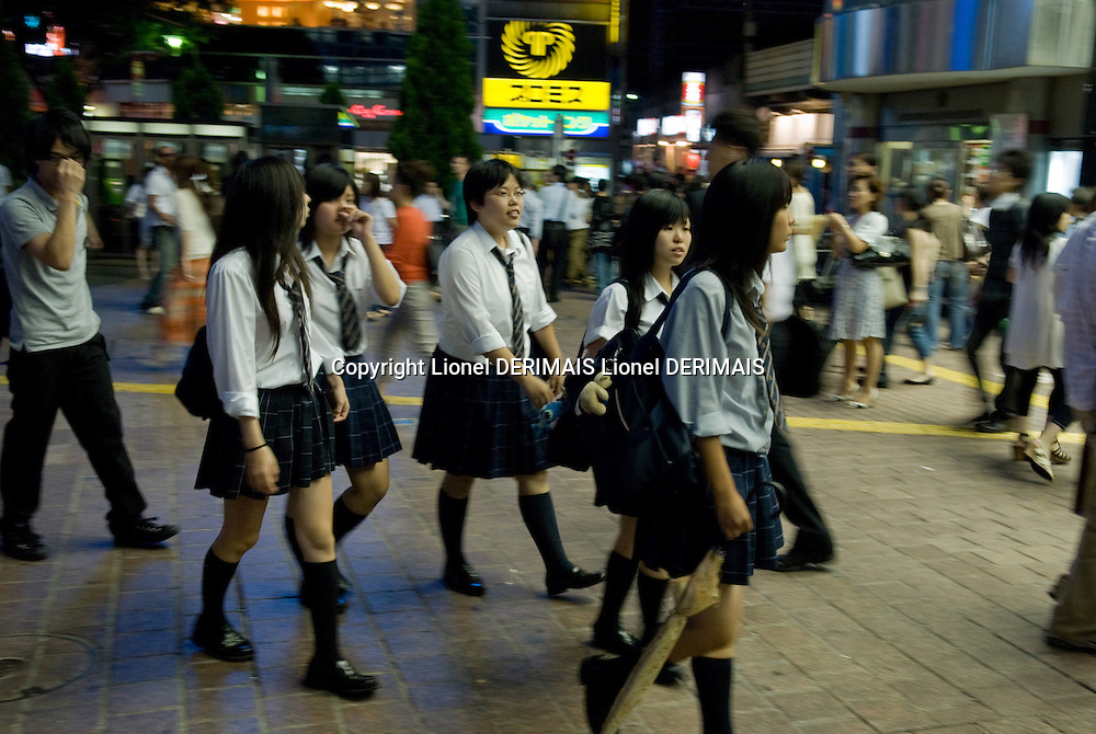 Schoolgirls on their way to catch their train home, Shibuya station, Tokyo, Japan.